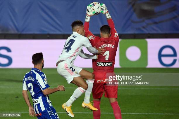 Alaves' Spanish goalkeeper Fernando Pacheco is challeged by Real Madrid's Dominicans forward Mariano Diaz as he makes a save during the Spanish...