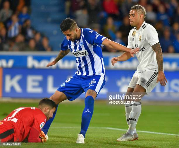 Alaves' Spanish goalkeeper Fernando Pacheco secures the ball in front of Alaves' Chilean defender Guillermo Maripan and Real Madrid's...