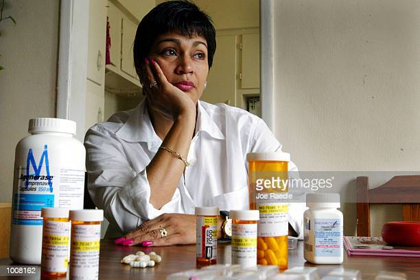 Alba Cerrato sits with her cocktail of 14 different AIDS medications that she takes three times a day July 11 2002 in Miami Florida Cerrato...