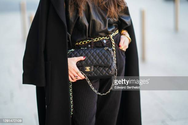 Alba Garavito Torre wears a black oversized leather top with puff sleeves from Munthe, a black wool long coat from Zara, a black leather quilted...
