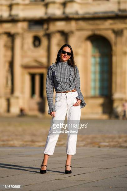Alba Garavito Torre wears a gingham checkered black and white shirt with Long Sleeve Ruffles from Serendipia, Mom jeans in white from Maison 123...