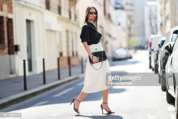 Alba Garavito Torre wears a one-shoulder / off-shoulder bi-color black and white midi dress with integrated belt from Natan, a black leather quilted...