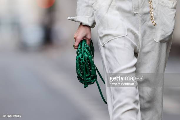Alba Garavito Torre wears a white jumpsuit with zipper long sleeves and rolled-up pants, a golden chain belt, a gold ring with stones, a green woven...