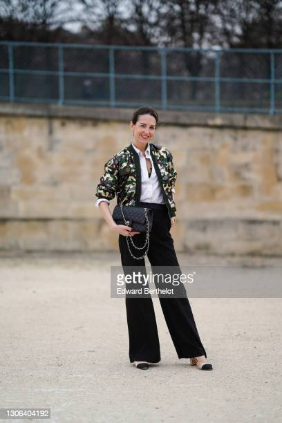 Alba Garavito Torre wears a white shirt from Zara, a green and khaki military print bomber jacket from Mr&Mrs Italy, a black leather quilted Chanel...