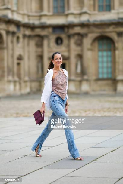 Alba Garavito Torre wears gold and pearl pendant earrings, a pale brown with gold embroidered flower pattern halter-neck asymmetric cropped t-shirt,...