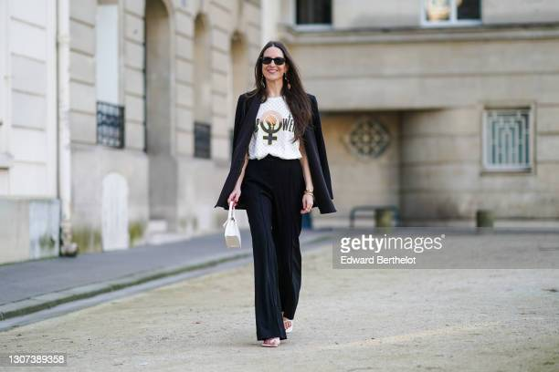 Alba Garravito Torre @albagaravitotorre wears Ray-Ban sunglasses, a total look Munthe made of a black blazer jacket, a white t-shirt with the printed...