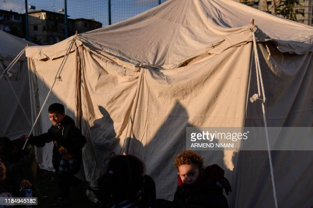 Albanian children stand next to a tent at a makeshift camp at the soccer stadium in Durres, western Albania on November 27 after the strongest...
