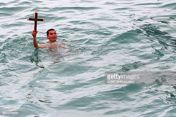 Albanian Enkel Sinani 19 years old holds a wooden cross after retrieved from the Adriatic Sea as part of Epiphany Day celebrations in Durres some 40...