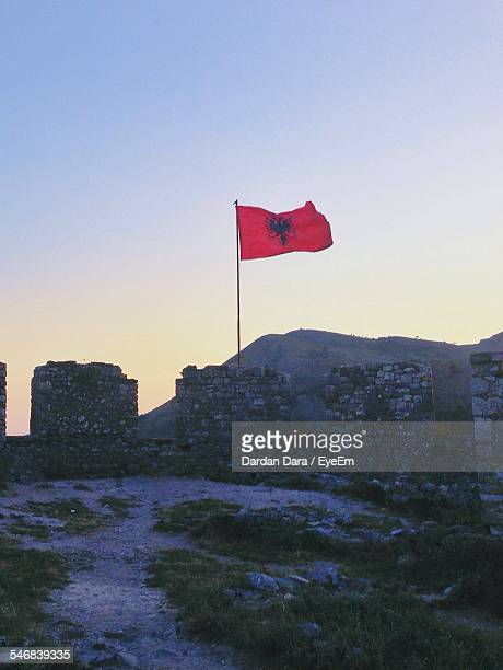 albanian flag on mountain against clear sky during sunset - bandiera albanese foto e immagini stock
