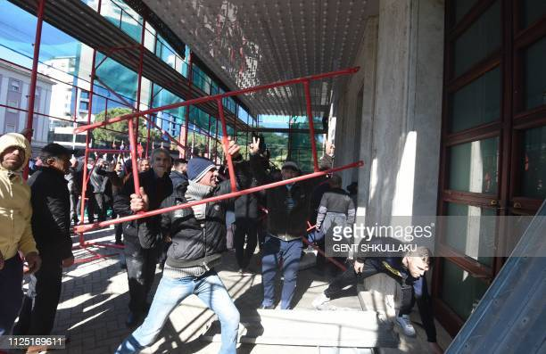 Albanian opposition supporters hit the doors of the government building during a protest demanding the resignation of Albanian Prime Minister Edi...