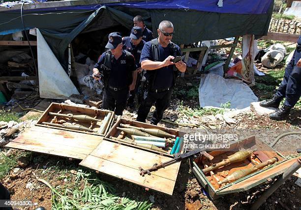 Albanian police officers take pictures of seized heavy guns in Lazarat village 230 kilometers south of the capital Tirana on June 20 2014 Police have...