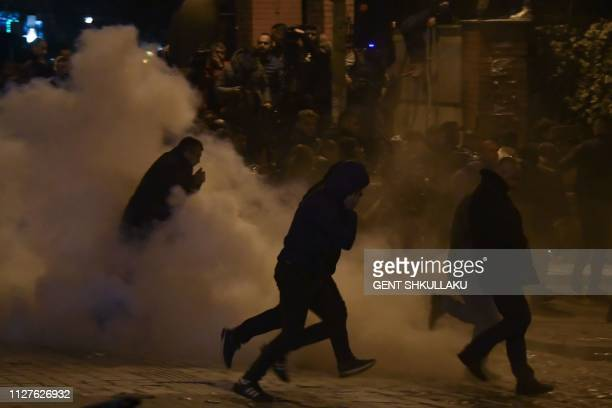 Albanian protesters run amid tear gas smoke during a demonstration held to demand the resignation of the Prime Minister on February 26 in Tirana...