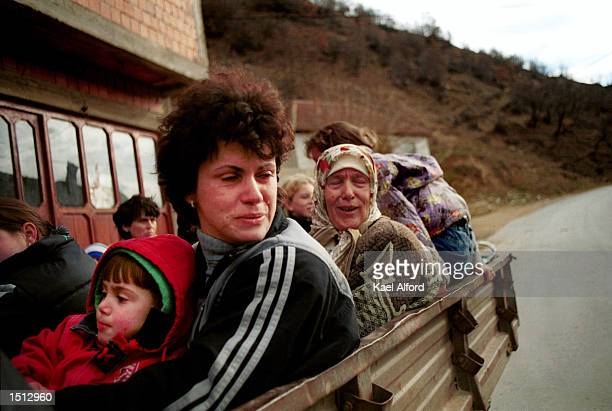 Albanian refugees from the Presevo valley pass through an American checkpoint November 26 2000 on the boundary of Kosovo Approximately 1200 refugees...