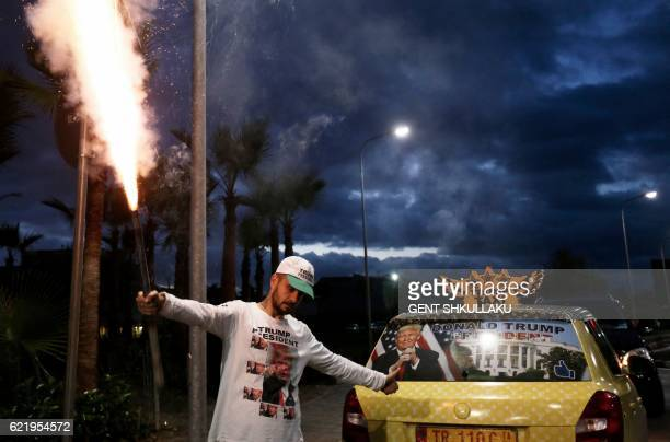 Albanian taxi driver Uljan Kolgjegja, 37 years old, holds a flare as he celebrates the victory of Republican candidate Donald Trump in the US...