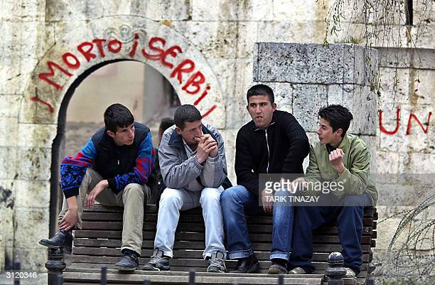 Albanian youths chat in front of a destroyed church in Prizren 22 March 2004 NATO is sending 2000 more troops to help the 17000 foreign troops and...