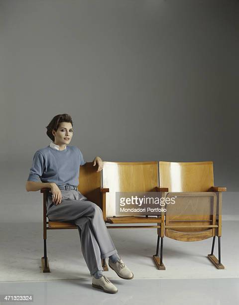 Albanianborn Italian singer Anna Oxa posing in man clothes sitting on some cinema chairs 1989