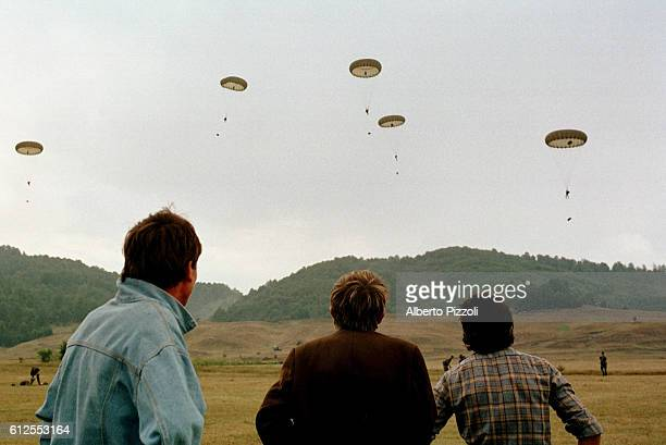 Albanians looking at UK paratroopers in training.