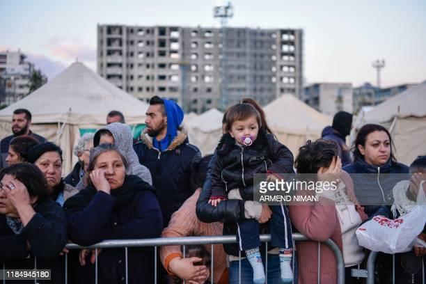 Albanians wait in line for food at a makeshift camp at the soccer stadium in Durres western Albania on November 27 after the strongest earthquake in...