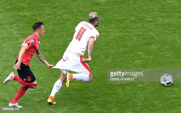 Albania's midfielder Ergys Kace pulls down the shorts of Switzerland's midfielder Valon Behrami during the Euro 2016 group A football match between...
