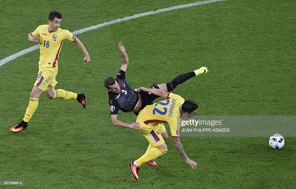 TOPSHOT - Albania's midfielder Ermir Lenjani (C) vies with Romania's defender Cristian Sapunaru (R) during the Euro 2016 group A football match between Romania and Albania at the Parc Olympique Lyonnais stadium in Lyon on June 19, 2016. / AFP / JEAN