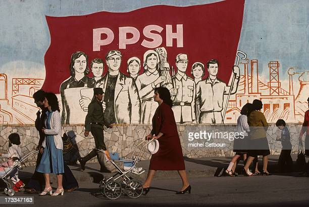CONTENT] Albanie Korcia at the end of the communist regime pedestrians pass by a Realistic socialist style painting with a slogan glory to the...