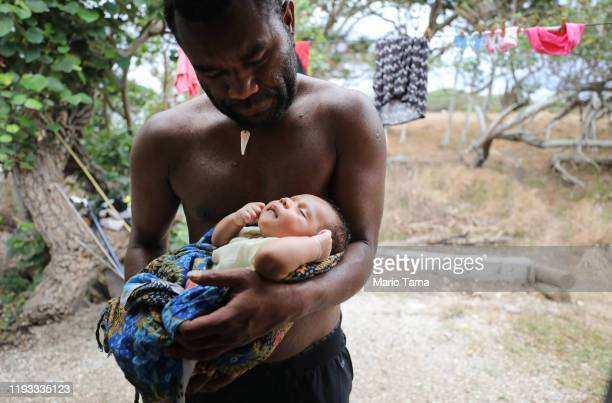 Albea Watt holds his baby son Tanny outside his home which was destroyed by Cyclone Pam and rebuilt on December 05 2019 in Tanna Vanuatu 25 percent...
