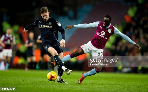 Albert Adomah of Aston Villa is challenged by Angus MacDonald of Barnsley during the Sky Bet Championship match between Aston Villa and Barnsley at...