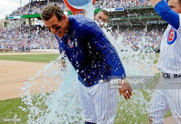 Albert Almora Jr #5 and Kyle Schwarber of the Chicago Cubs douse Anthony Rizzo after his walkoff home run in a win over the Arizona Diamondbacks at...