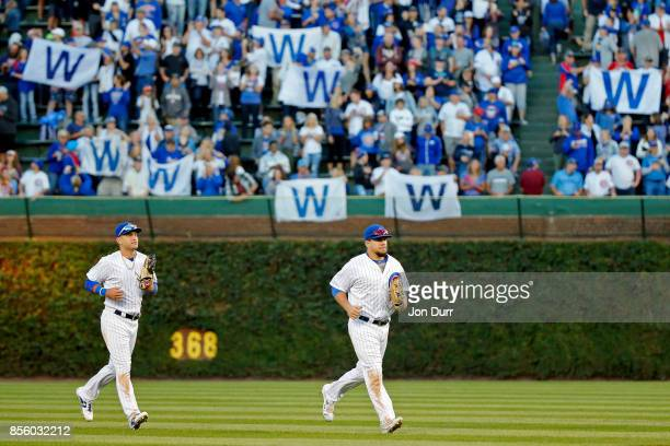 Albert Almora Jr #5 of the Chicago Cubs and Kyle Schwarber jog back to the dugout after their win over the Cincinnati Reds as fans hold up 'W' flags...