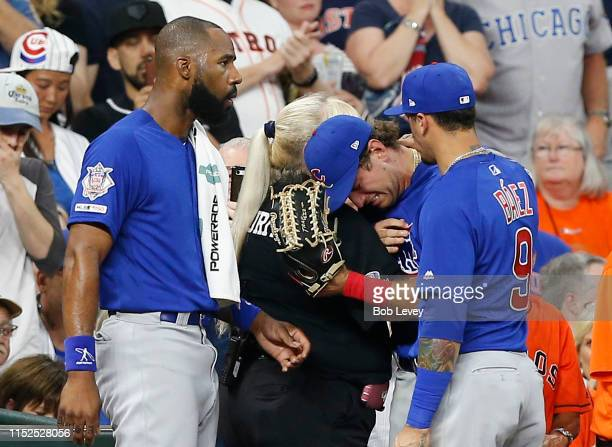 Albert Almora Jr #5 of the Chicago Cubs center is comforted by Jason Heyward and Javier Baez after checking on a young child that was struck by a...
