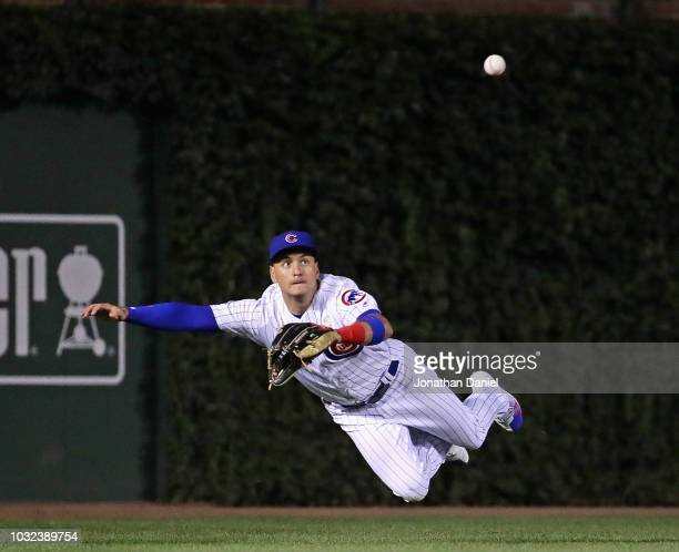 Albert Almora Jr #5 of the Chicago Cubs dives to catch a ball hit by Mike Moustakas of the Milwaukee Brewers in the 6th inning at Wrigley Field on...
