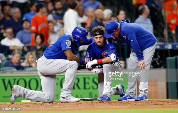 Albert Almora Jr. #5 of the Chicago Cubs is comforted by manager Joe Maddon and Jason Heyward after a young child was injured on foul ball off his...