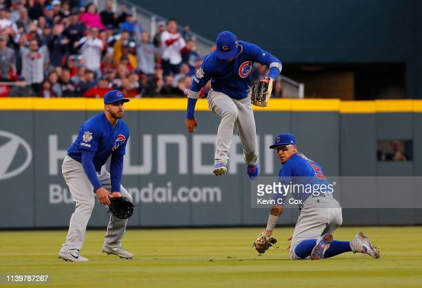 Albert Almora Jr #5 of the Chicago Cubs leaps over Javier Baez as Baez picks up a popup double hit by Ozzie Albies of the Atlanta Braves in the first...