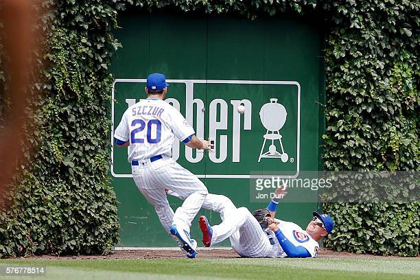 Albert Almora Jr #5 of the Chicago Cubs tosses the ball to Matt Szczur after making a catch and colliding with the wall against the Texas Rangers...