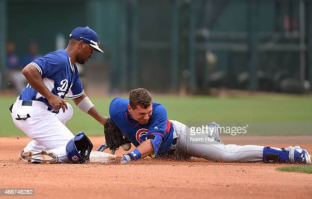 Albert Almora of the Chicago Cubs slides safely into second base knocking the ball out of the glove of Jimmy Rollins of the Los Angeles Dodgers...