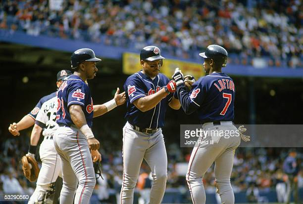 Albert Belle of the Cleveland Indians is greeted by Kenny Lofton and Julio Franco during an MLB game at Tiger Stadium in Detroit Michigan John...