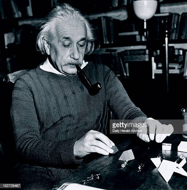 Albert Einstein at Princeton USA 4 February 1944 The physicist philosopher and humanitarian Albert Einstein solving a puzzle whilst smoking a pipe...