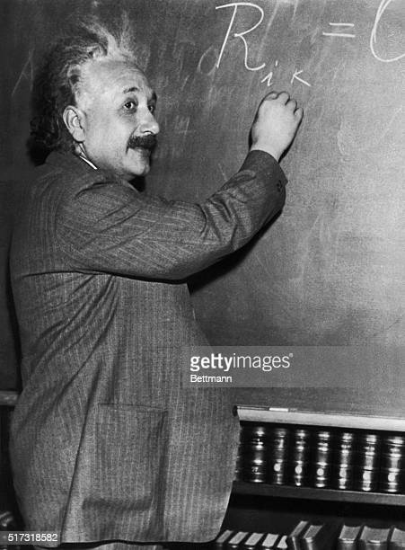 Albert Einstein demonstrates mathematical formulas on a blackboard in front of California scientists