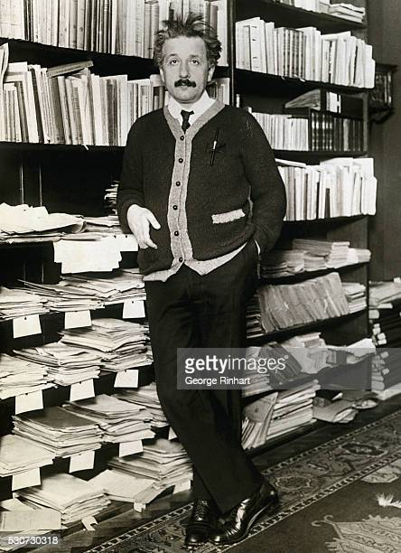 Albert Einstein leaning against shelves of scientific books and papers at his home in Berlin after his return from a visit to the United States