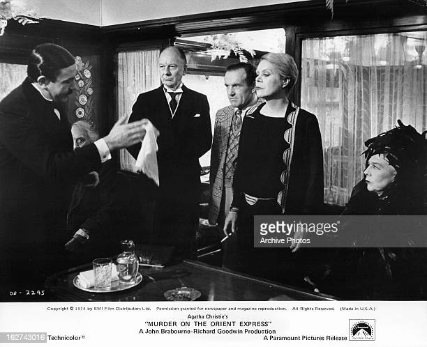 Albert Finney holds a napkin to Rachel Roberts in a scene from the film 'Murder On The Orient Express' 1974 John Gielgud stands behind