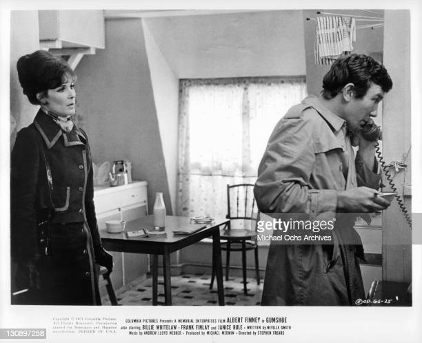 Albert Finney is on the phone as Janice Rule enters the room in a scene from the film 'Gumshoe' 1971