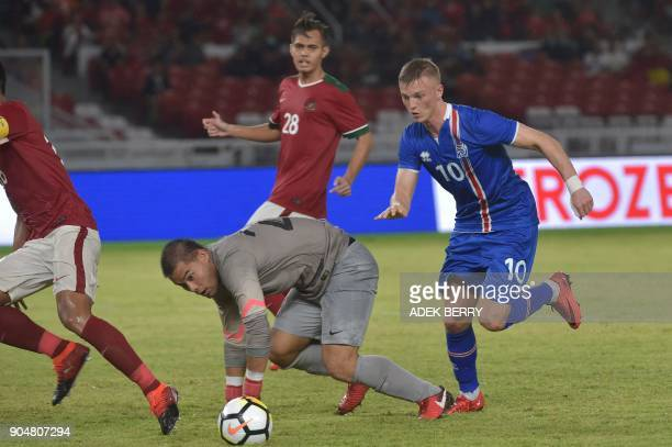 Albert Gudmundsson of Iceland vies for a ball with Indonesian goal keeper Andritany Ardhiyasa as M Rezaldi Hehanusa looks on during a friendly match...