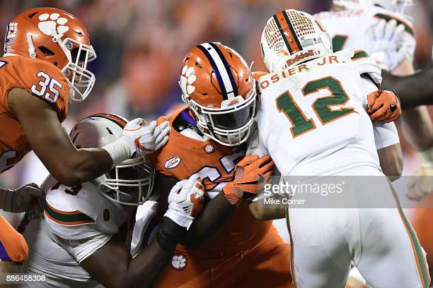 Albert Huggins of the Clemson Tigers leads a tackle on Malik Rosier of the Miami Hurricanes during the ACC Football Championship at Bank of America...