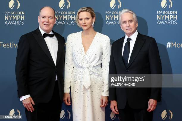Albert II of Monaco and his wife Charlene of Monaco pose with US actor Michael Douglas who'll receive a Golden Nymph Award for his career during the...