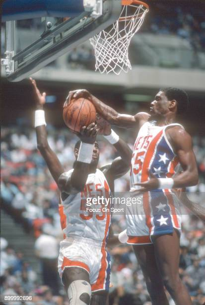 Albert King and Darryl Dawkins of the New Jersey Nets fights for a rebound during an NBA basketball game circa 1986 at the Brendan Byrne Arena in...
