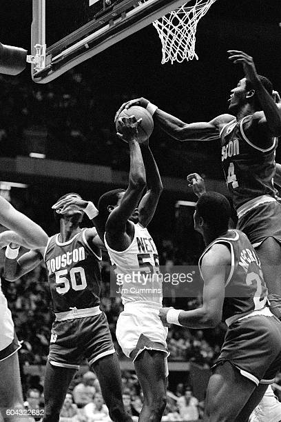 Albert King of the New Jersey Nets and Hakeem Olajuwon of the Houston Rockets go after a rebound circa 1985 at Brendan Byrne Arena in East Rutherford...