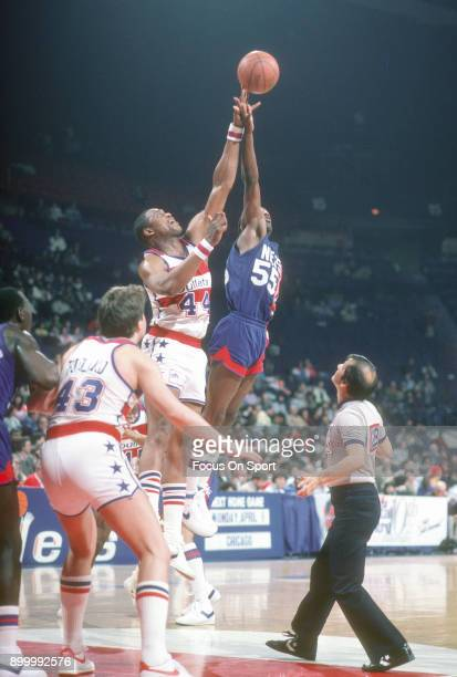 Albert King of the New Jersey Nets battles for a jump ball with Rick Mahorn of the Washington Bullets during an NBA basketball game circa 1984 at the...