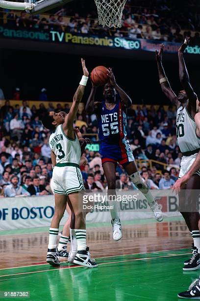 Albert King of the New Jersey Nets goes up for a shot against Dennis Johnson of the Boston Celtics during a game played in 1987 at the Boston Garden...