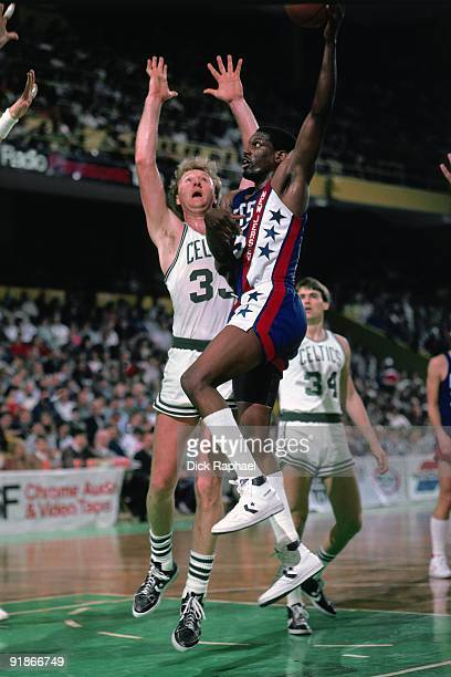 Albert King of the New Jersey Nets goes up for a shot against Larry Bird of the Boston Celtics during a game played in 1986 at the Boston Garden in...