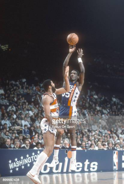 Albert King of the New Jersey Nets shoots over Greg Ballard of the Washington Bullets during an NBA basketball game circa 1984 at the Capital Centre...